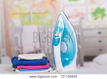 Steam iron and ironing clothes on the background of the room.