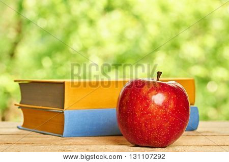 Apple and stack of books on the wooden table on green background