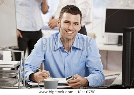 Casual young businessman working in office, sitting at desk, writing notes to personal organizer.