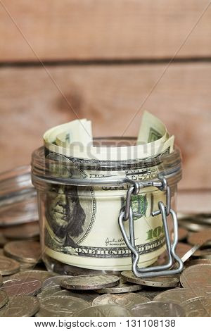 Glass jar with dollar banknotes on a pile of coins