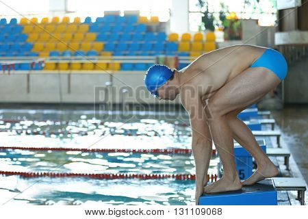 Sporty young man preparing to jump into the water in the swimming pool