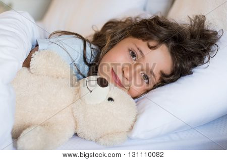 Young cute child sleeping on bed under blanket during the afternoon. Girl lying in bed looking at camera. Close up face of little girl embracing her teddy bear and sleeping.