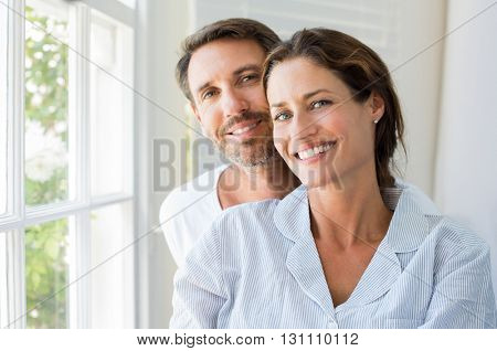 Happy young couple sitting near window in the bedroom. Portrait of smiling man and woman looking at camera at home. Couple in pajamas during the morning.