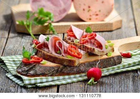 Slices of Bavarian sausage on farmhouse bread, garnished and served on a rustic wooden board