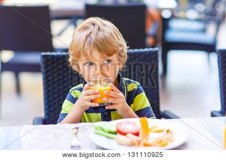 Little kid boy having healthy breakfast in hotel restaurant or city cafe. Cute child drinking juice and eating fresh vegetables