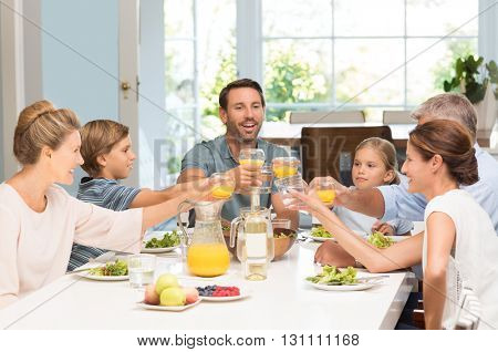 Smiling generation family raising glasses together in the kitchen. Happy parents with children and grandparents celebrating with a toast. Cheerful family raising toast with juice at dining table.
