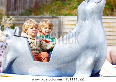Two little funny kid boys riding on animal on roundabout carousel in amusement park. Happy children, twins having fun outdoors on sunny day.