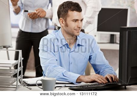 Casual businessman working in office, sitting at desk, typing on keyboard, looking at computer screen.?