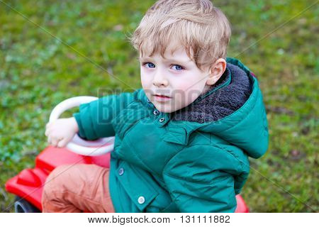 Little todder boy playing with big toy pedal car. Blond happy funny kid having fun on warm spring day.
