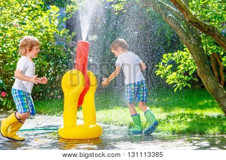 Two funny little friends playing together and splashing with a garden hose and sprinkler on hot and sunny summer day. Kid boys having fun outdoors.