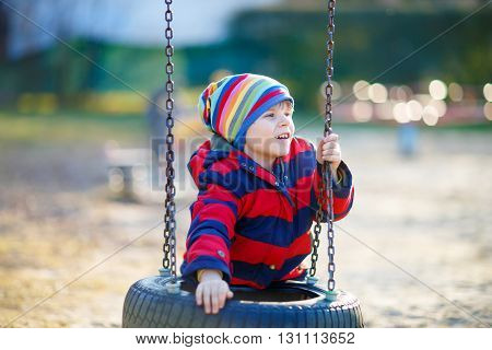 Happy little kid boy having fun with chain swing on outdoor playground. child swinging on warm sunny spring or autumn day. Active leisure with kids. Boy wearing colorful clothes