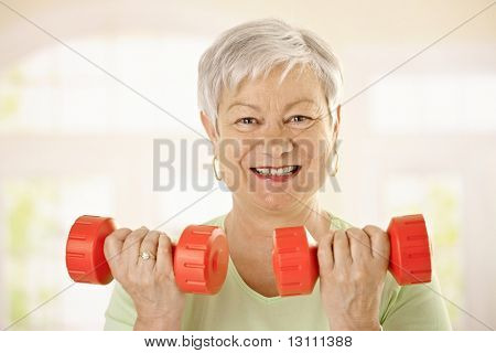 Closeup portrait of active senior woman doing dumbbell exercises at home, smiling.?