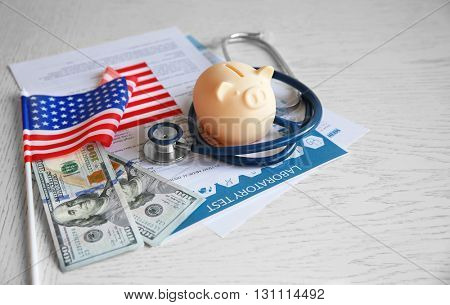 American medicine concept. Piggy bank, stethoscope and money on white wooden background