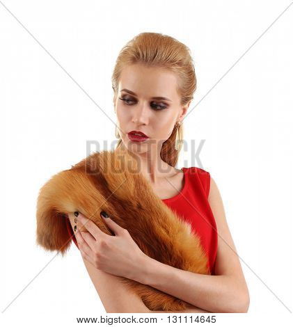 Young beautiful blonde girl wearing perfect makeup and red dress posing in a fox fur over white studio background