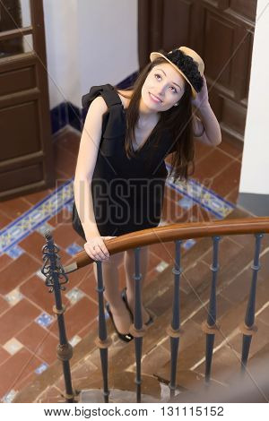 Attractive elegant woman in black dress and hat looking up while standing on steps and holding railing