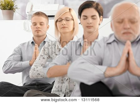 Businessteam doing yoga exercise in office together, sitting on floor with eyes closed.?