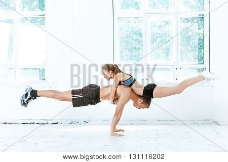 The fit woman and man doing some push ups at the gym on white background