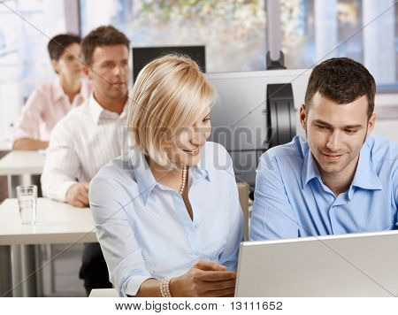Young business people sitting at desk, using computer at business training, smiling.?