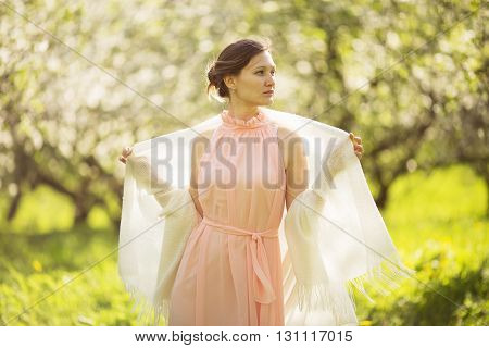 Beautiful girl in a dress and shawl in the apple orchard