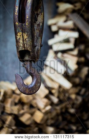 big rusty steel hook weighs on the background of wooden bars