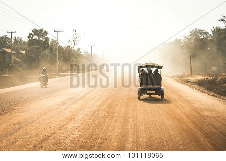 A tuk-tuk driving on a wide dirt road in Cambodia