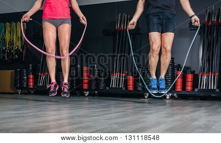 People legs doing exercises with jumping ropes in sports center