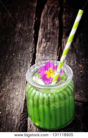 Green smoothie edible blossoms on old wooden table