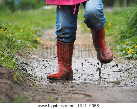 child's feet in the muddy, wet jeans and rubber boots. The child jumps in a puddle