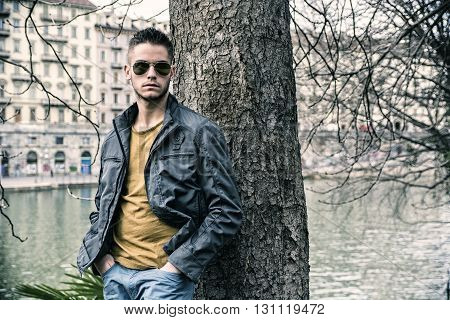 Three-quarter length of contemplative light brown haired young man wearing grey jacket and denim jeans standing beside picturesque river in Turin, Italy