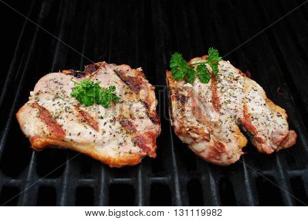Two Perfectly Cooked Pork Chop on a Grill Garnished with Fresh Parsley