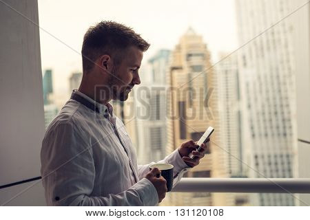 Man enjoying a coffee break and looking at a mobile phone.