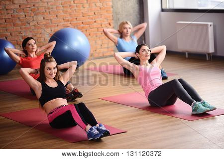 Attractive fit girls are doing sit-ups in gym. They are smiling