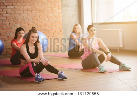 Cheerful young women are resting after exercising. They are sitting on carpets and relaxing. The ladies are looking at camera and smiling