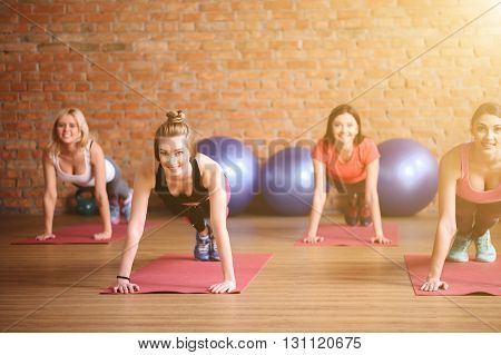 Beautiful fit girls are doing push-ups in gym. They are looking forward and smiling