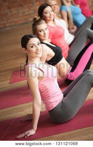 Cute sporty girls are doing exercises together. They are sitting and posing. The ladies are smiling