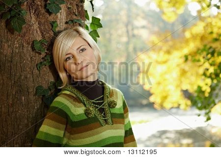 Outdoors portrait of happy young woman standing in autumn park at tree.?