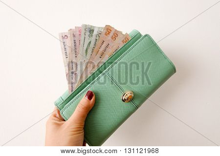 A hand holding Money in purse on white BG