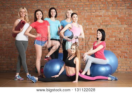 We like sport. Cute group of young women are standing and smiling in gym. Their female trainer is doing splits. Another woman is sitting on fitness ball