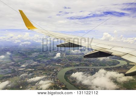 View from airplane window. Wing of an airplane flying above the clouds over river Thailand