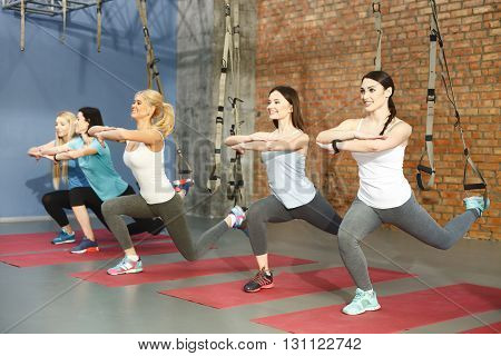 Cheerful sporty group is doing exercise with trx fitness straps. Women are doing sit-ups and smiling
