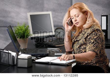 Senior woman sitting at office desk talking on mobile phone matching dates from personal organizer.?
