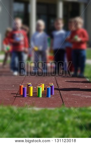 Children playing with homemade do-it-yourself educational toys tube bowling. Learning through experience concept gross and fine motor skills educational approach concept.