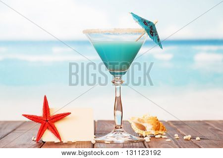 Blank card, cocktail, starfish and shell in the sand against the sea.