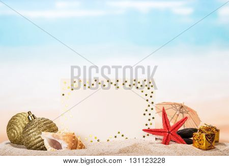 Blank greeting, sea shells and a star, Christmas toys, gifts in the sand against the sea.