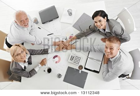 Confident businessteam holding hands at meeting over table expressing teamwork and unity, smiling at camera, overhead view.?