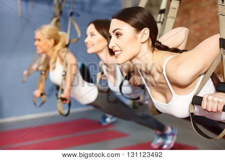 Beautiful young women do push ups in gym. They are leaning their hands on the trx straps and smiling