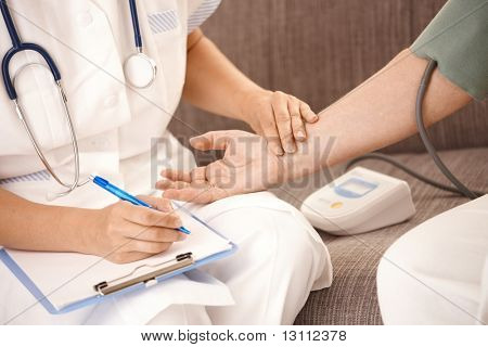 Closeup of nurse measuring blood pressure and checking heartbeat on senior woman's wrist.?