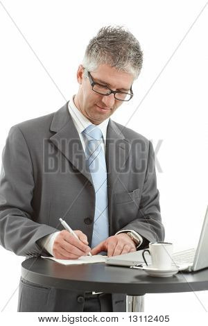 Businessman standing at coffee table writing notes. Isolated on white background.?