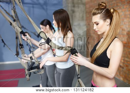 Cheerful young women are adjusting trx fitness straps before training. They are standing and looking at ropes with concentration