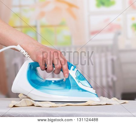 Woman's hand stroking the clothes steam iron on the background of the room.